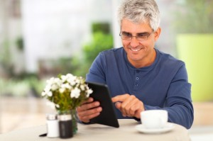 middle aged man surfing the internet using tablet computer
